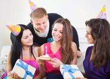 Menina alegre na festa de anos cercada por amigos no partido Fotos de Stock