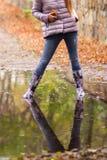 Menina alegre nas botas de borracha que saltam em poças após a chuva foto de stock royalty free