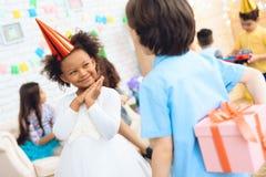 A menina alegre no chapéu do aniversário espera-a para receber a caixa de presente Tempo do presente Fotografia de Stock Royalty Free