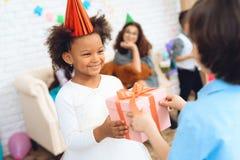 A menina alegre no chapéu do aniversário espera-a para receber a caixa de presente Tempo do presente Imagem de Stock Royalty Free