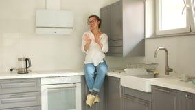 Menina alegre no estilo ocasional em sua cozinha nova após a conclusão dos reparos Uma mulher está sentando-se em um tabletop nov vídeos de arquivo