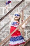 Menina alegre nos óculos de sol que estão em escadas e com girândola fotos de stock