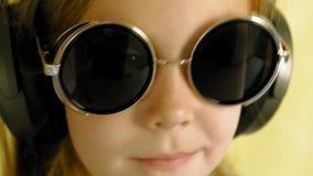 Menina alegre nos fones de ouvido em um fundo amarelo Retrato do close up filme
