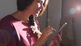 A menina alegre nova está guardando um telefone em sua mão e está escrevendo algo, HD video estoque