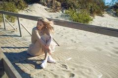 Menina alegre nova no litoral Mulher loura nova que senta-se na areia e que aprecia o tempo agradável Foto de Stock