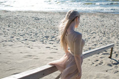 Menina alegre nova no litoral A mulher loura nova vai ao mar Saia bege na moda Imagem de Stock