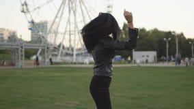 Menina alegre nova no parque ensolarado do verão que abre suas mãos aos lados ao andar no parque video estoque
