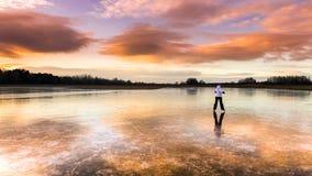 Menina alegre nova que patina no lago Imagens de Stock