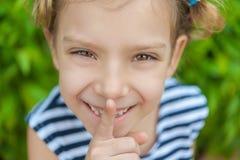 A menina alegre põe o indicador aos bordos Fotos de Stock