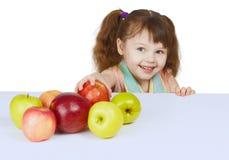 Menina alegre pequena com maçãs Fotos de Stock Royalty Free
