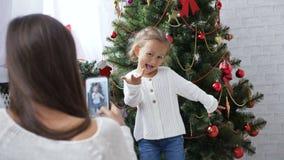Menina alegre que dança e que joga o macaco perto da árvore de Natal video estoque