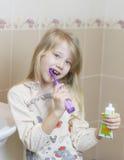 Menina alegre que escova seus dentes na escova de dentes nova do banheiro fotos de stock