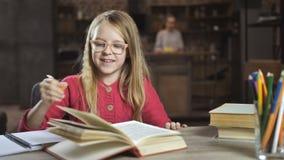 Menina alegre que escreve lhe trabalhos de casa para a escola vídeos de arquivo