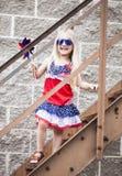 Menina alegre que está em escadas nos óculos de sol e com girândola foto de stock royalty free