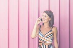 Menina alegre que fala no telefone celular no fundo cor-de-rosa foto de stock royalty free