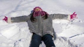 Menina alegre que faz o anjo da neve vídeos de arquivo