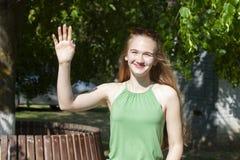 Menina alegre que faz o gesto do tiro da arma Jovem mulher bonita no tempo de lazer de aprecia??o ocasional no parque da cidade,  fotos de stock