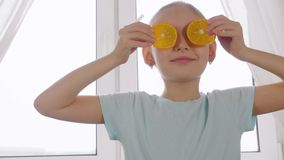 Menina alegre que guarda os olhos dianteiros das fatias alaranjadas no fundo da janela da cozinha filme