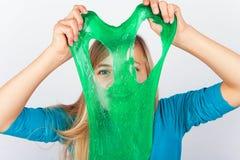 Menina alegre que guarda um limo verde e que olha através de seu furo fotografia de stock