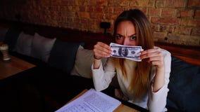Menina alegre que joga com dinheiro no café e no sorriso video estoque
