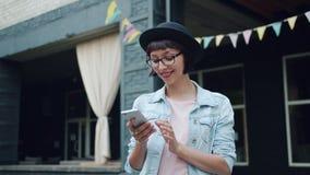 Menina alegre que olha a tela do smartphone que sorri obtendo a boa notícia fora video estoque