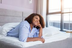 Menina alegre que pensa sobre seu noivo ao descansar na cama confortável imagem de stock royalty free