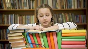 Menina alegre que ri ao ler um livro na biblioteca video estoque
