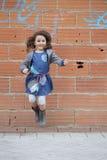 Menina alegre que salta contra da parede de tijolo imagens de stock