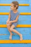 Menina alegre que senta-se na ponte de madeira Fotos de Stock Royalty Free