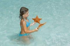 Menina alegre que senta-se no oceano claro dos azuis celestes e que olha a estrela do mar Fotos de Stock