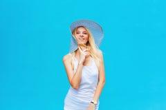 Menina alegre que smilling em um fundo azul com um chapéu Fotografia de Stock Royalty Free