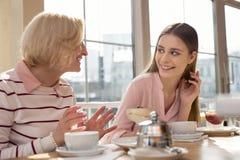 Menina alegre que tem o almoço com sua avó Imagens de Stock Royalty Free