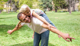 Menina alegre que tem o divertimento com seu pai Fotografia de Stock