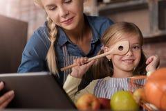 Menina alegre que tem o divertimento com sua mãe na cozinha fotografia de stock royalty free