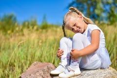 A menina alegre senta-se em uma pedra na rua e sorri-se em um dia ensolarado fotografia de stock