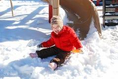 A menina alegre senta-se na neve no campo de jogos Fotografia de Stock Royalty Free