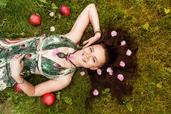 Menina alternativa ruivo de sorriso com caminhadas barbeadas em um pomar de Sunny Apple em um dia de verão ensolarado imagem de stock