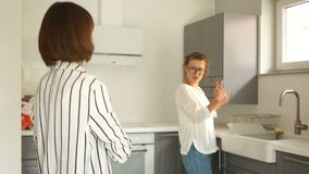 A menina aluga um apartamento e inspeciona a cozinha Uma moça obtém as chaves a seu apartamento novo das mãos de vídeos de arquivo