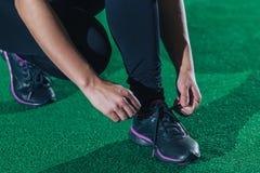 A menina amarra acima laços antes de treinar em um gym em um assoalho verde, crossfit Fim acima Fotografia de Stock
