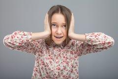 A menina amedrontada fecha suas orelhas com mãos Fotos de Stock