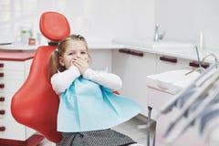 A menina amedrontada no escritório do dentista cobriu a boca com as mãos fotografia de stock royalty free