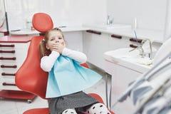 A menina amedrontada no escritório do dentista cobriu a boca com as mãos foto de stock