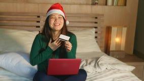 Menina americana asiática feliz e bonita no chapéu de Santa Christmas usando o cartão de crédito e no laptop para a compra em lin vídeos de arquivo