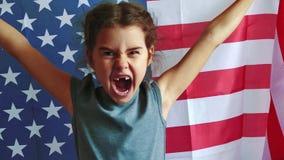 Menina americana com bandeira americana em um fundo alegria de ondulação da felicidade da menina e da bandeira americana forte filme