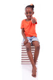 Menina americana do africano negro bonito assentada em uma pilha de vaia Foto de Stock