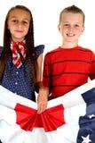 Menina americana e menino que guardam o sorriso patriótico da bandeira Fotografia de Stock Royalty Free
