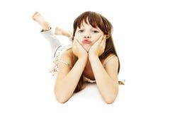 Menina amuando que encontra-se no assoalho foto de stock
