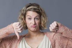 Menina amuando que expressa a dúvida, o desacordo ou o desagrado com polegares para baixo Imagens de Stock Royalty Free