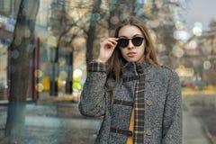 A menina anda abaixo da rua e endireita seus óculos de sol Imagem de Stock