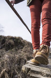 A menina anda ao longo da ponte de madeira podre velha em botas à moda imagens de stock